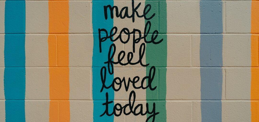 Wand mit der Aufschrift - make people feel loved again